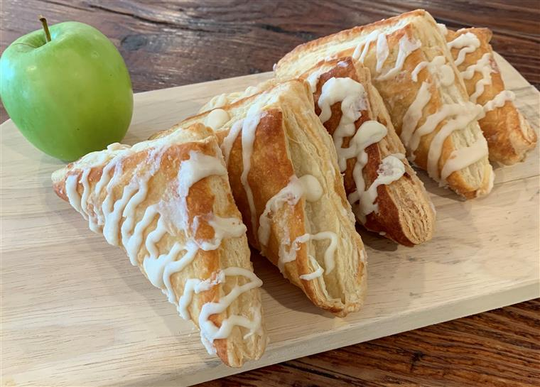fresh apple turnover pastries on the wood table with a granny smith apple to the side.