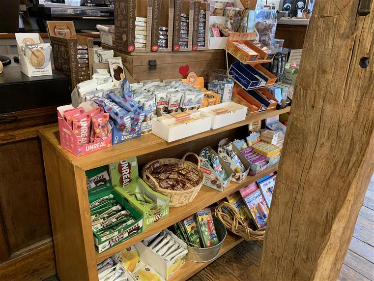 wood shelves with assorted candies in baskets by the register