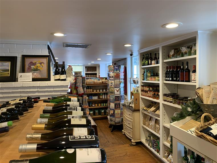 Corner of the store with shelves of assorted wine bottles.