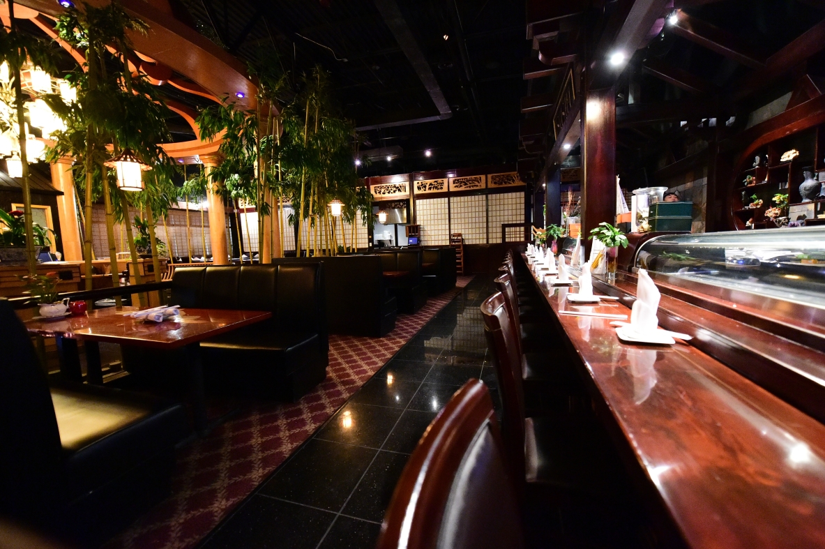 view of the sushi bar. booths in front and bamboo for decoration