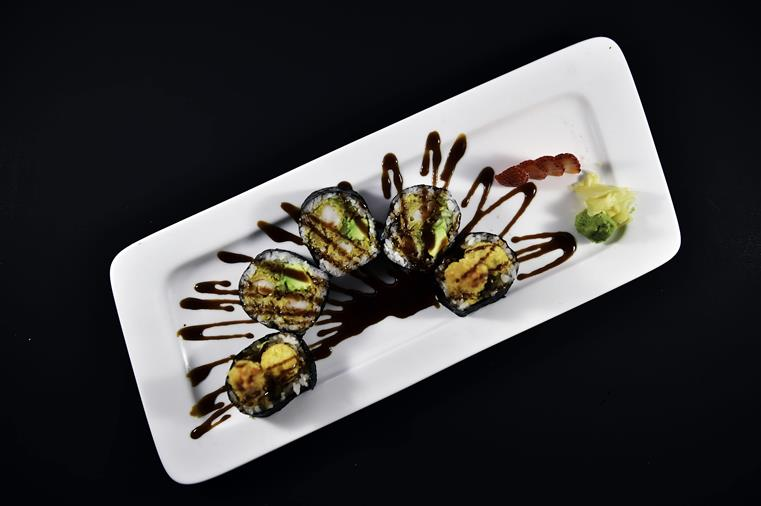 shrimp tempura roll on a white plate with a black sauce drizzle