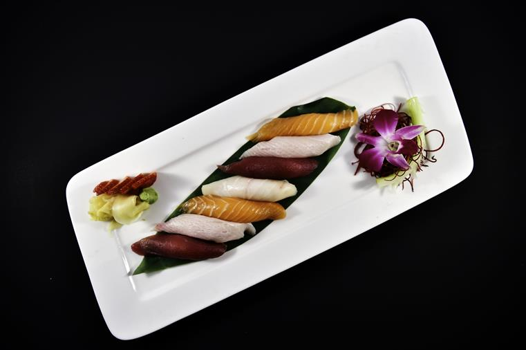 sushi regular lined up on a plate with a flower garnish