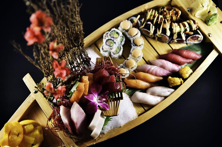 plate of assorted sushi rolls and sashimi