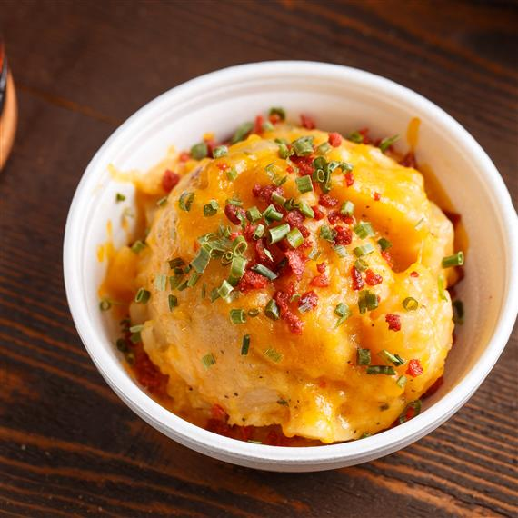 A bowl of mashed potatoes topped with cheese, bacon bits, and scallions
