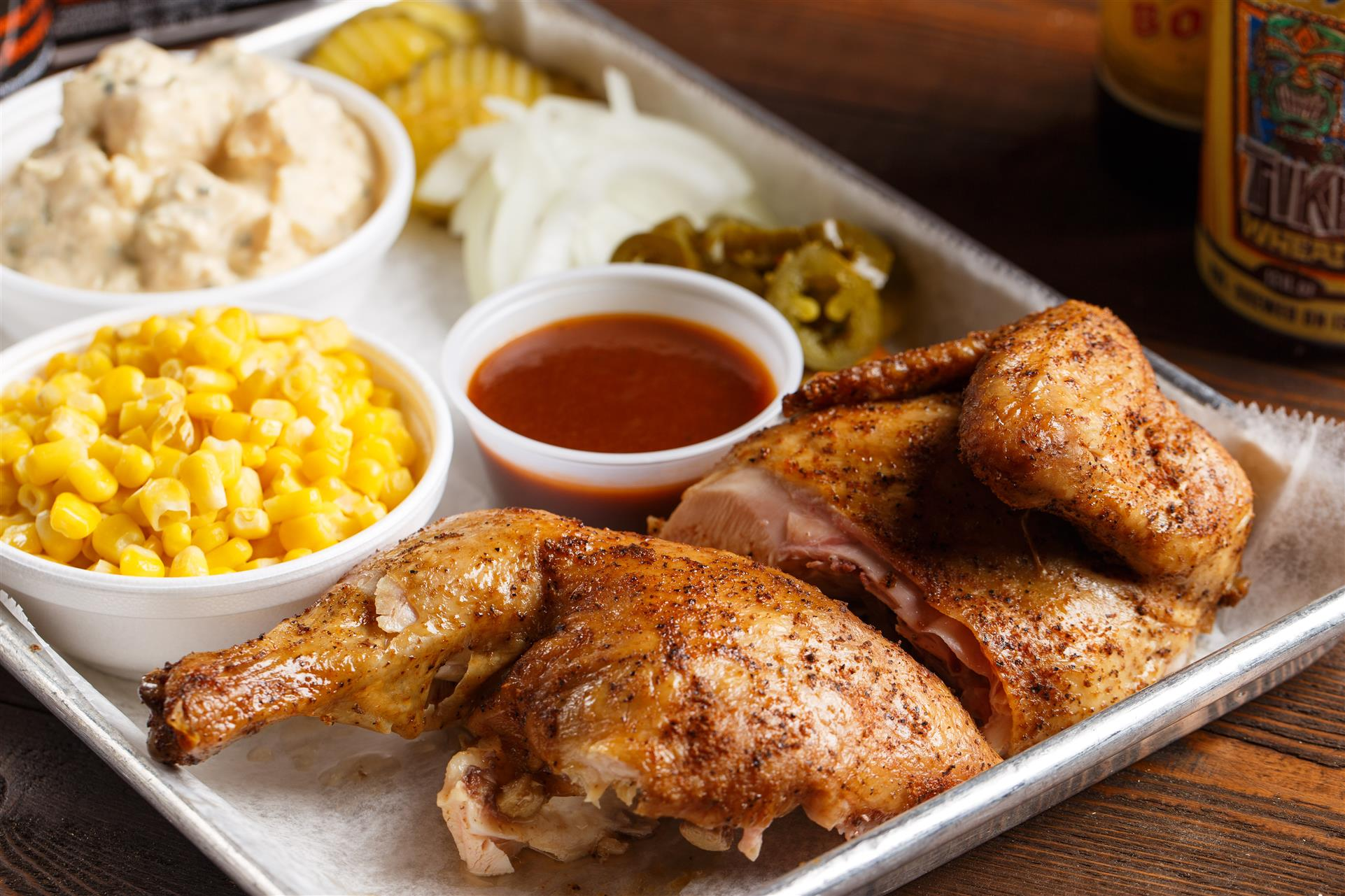 Roasted BBQ chicken with a side of corn and BBQ sauce