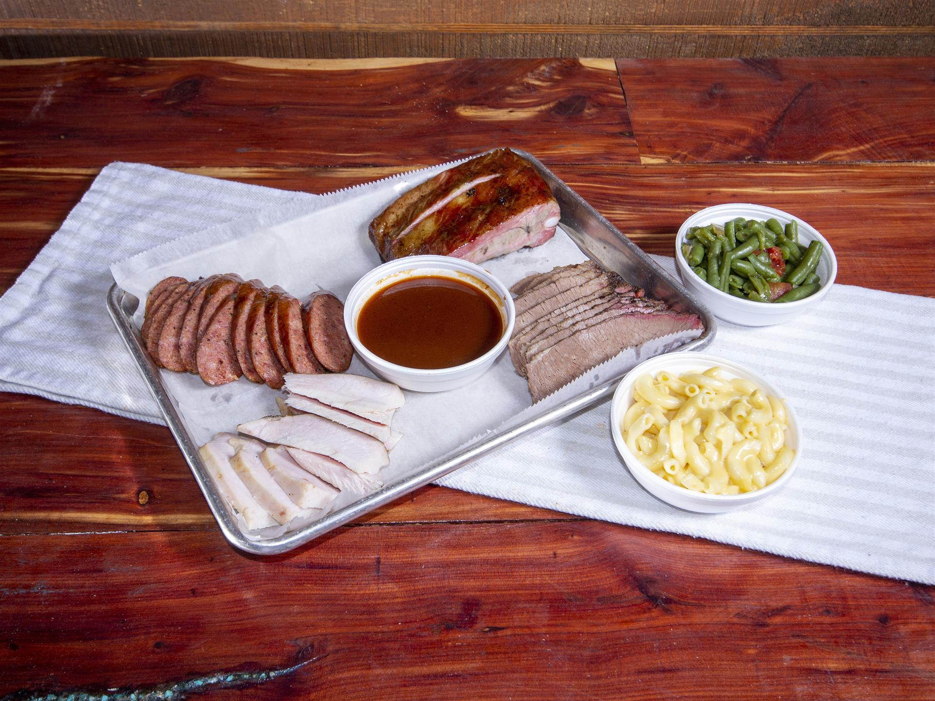 The four meat tray which includes sausage, ribs, turkey, and brisket, with a side of macaroni and cheese and cut green beans