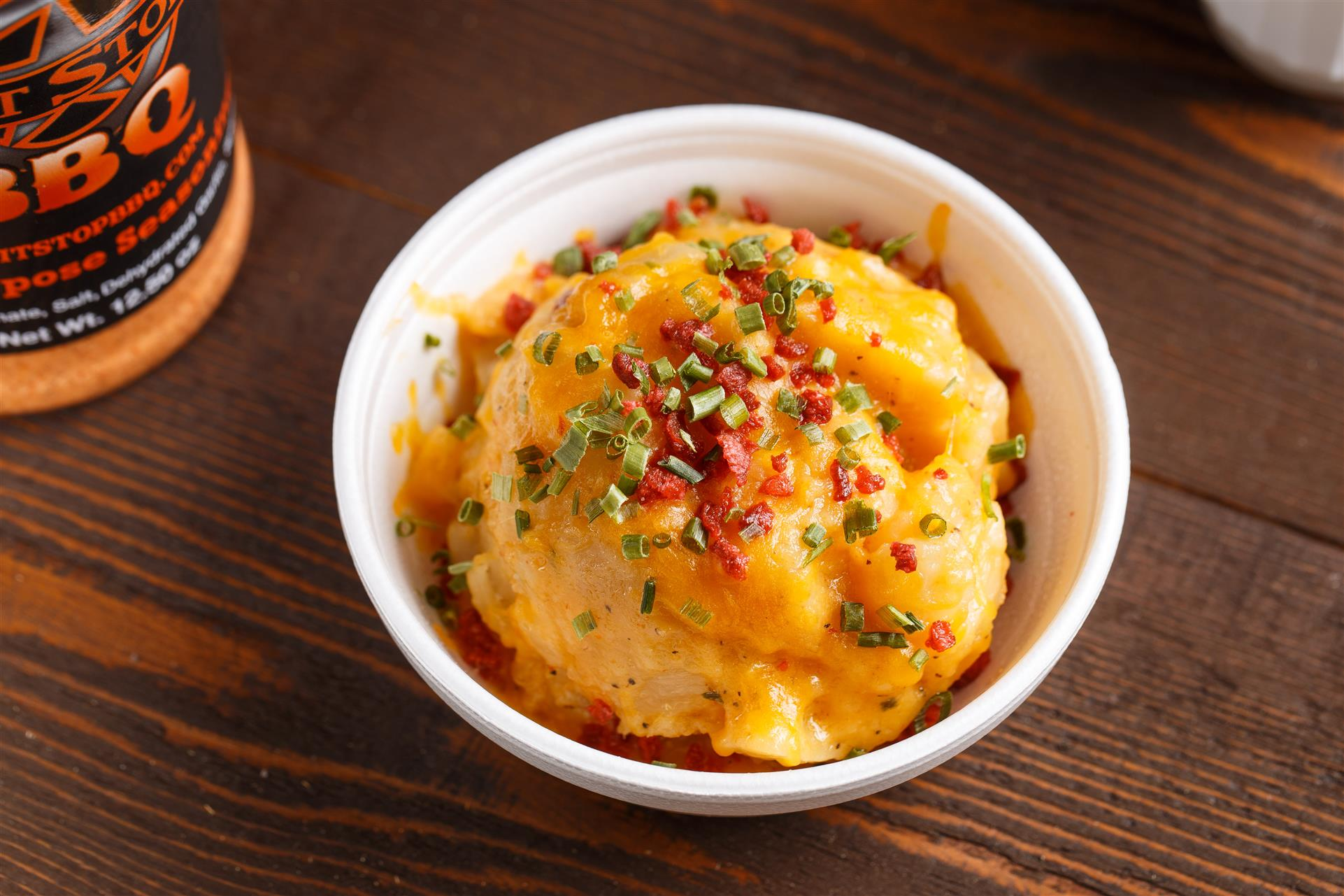 A bowl of mashed potatoes, covered in cheese, scallions, and bacon bits