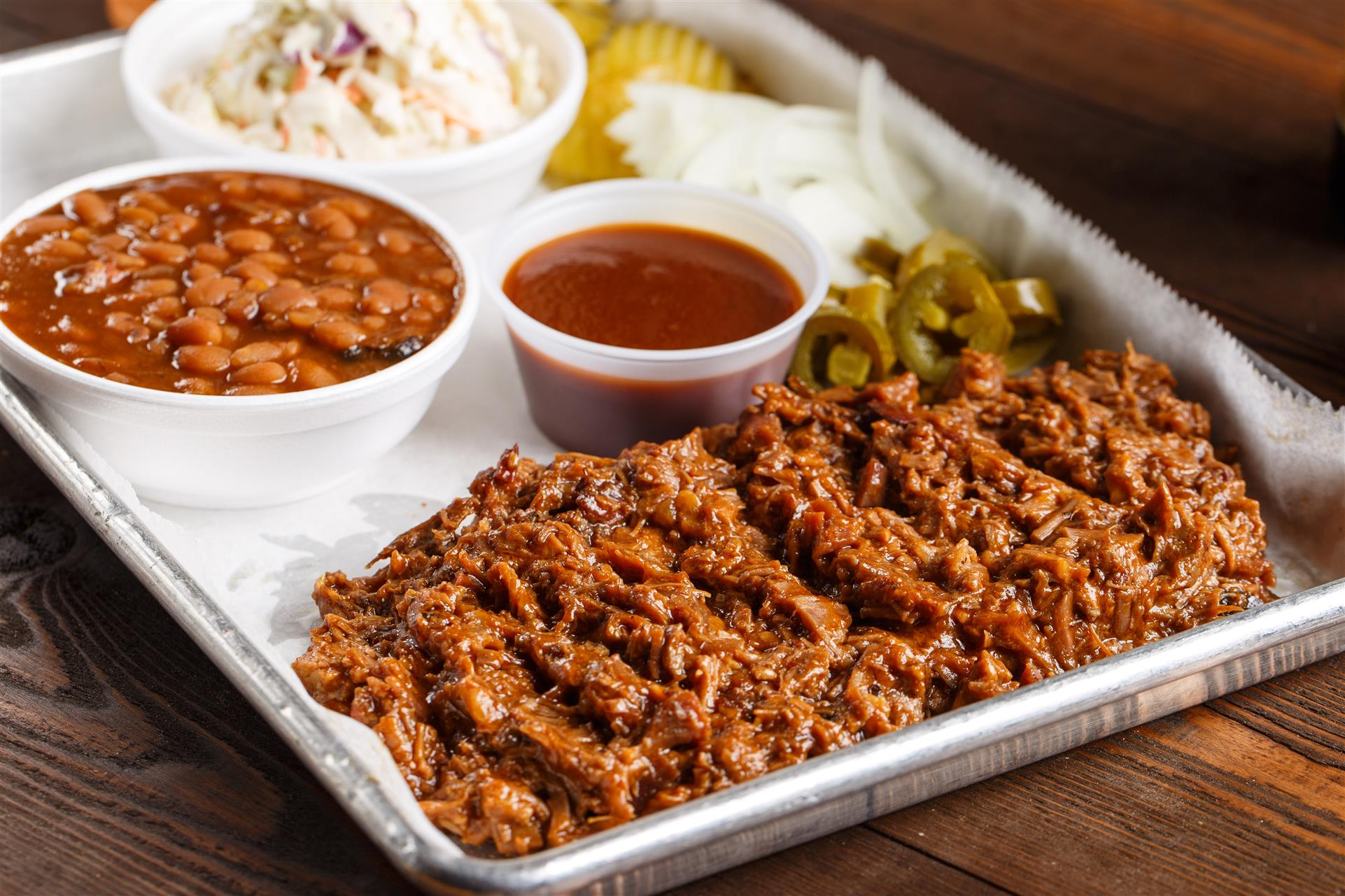 A tray of pulled pork with sides such as, coleslaw, baked beans, and BBQ sauce