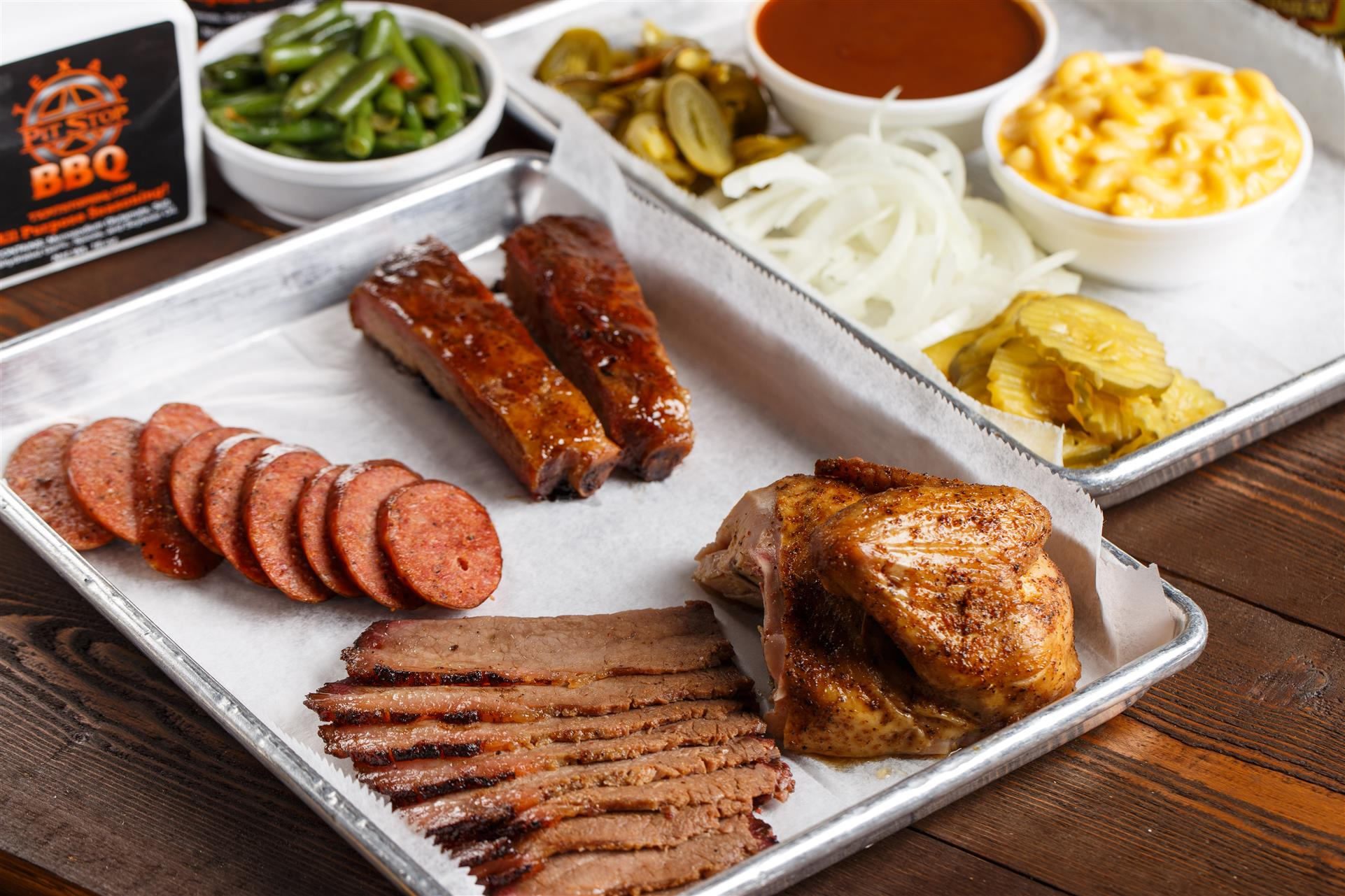 A tray of sausage, ribs, roasted BBQ chicken, and sliced brisket