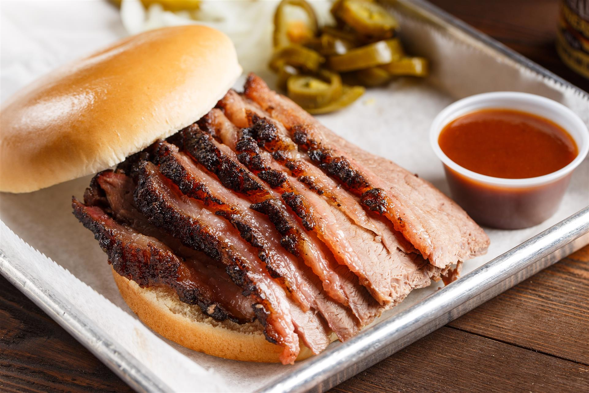 Sliced Brisket on a roll with a side of BBQ sauce