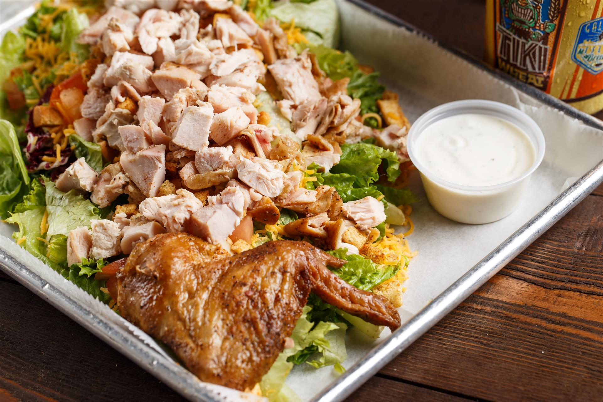 Roasted chicken cut up over a lettuce, croutons, cheese, and tomatoes
