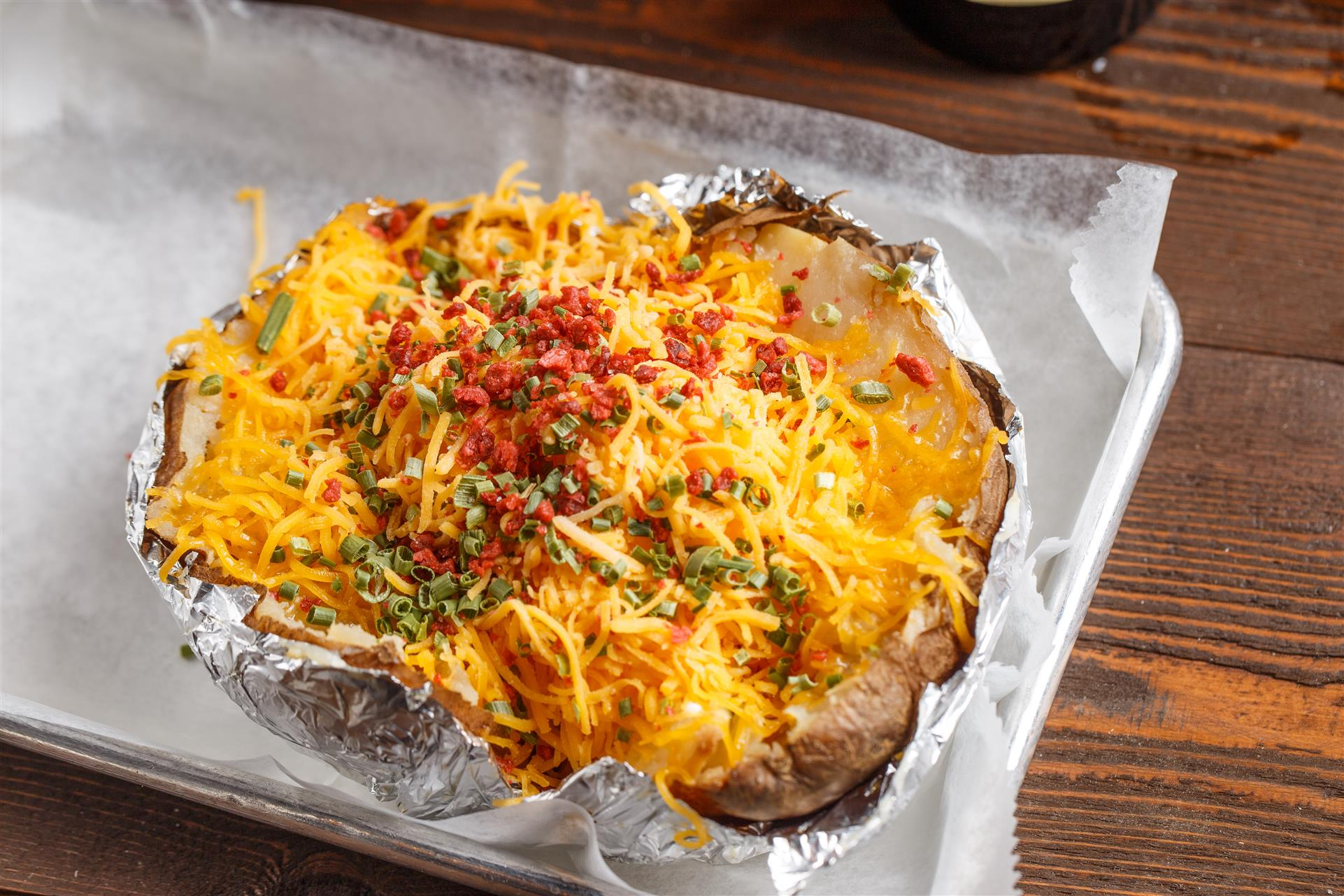 A baked potato covered with cheese, bacon bits, and scallions