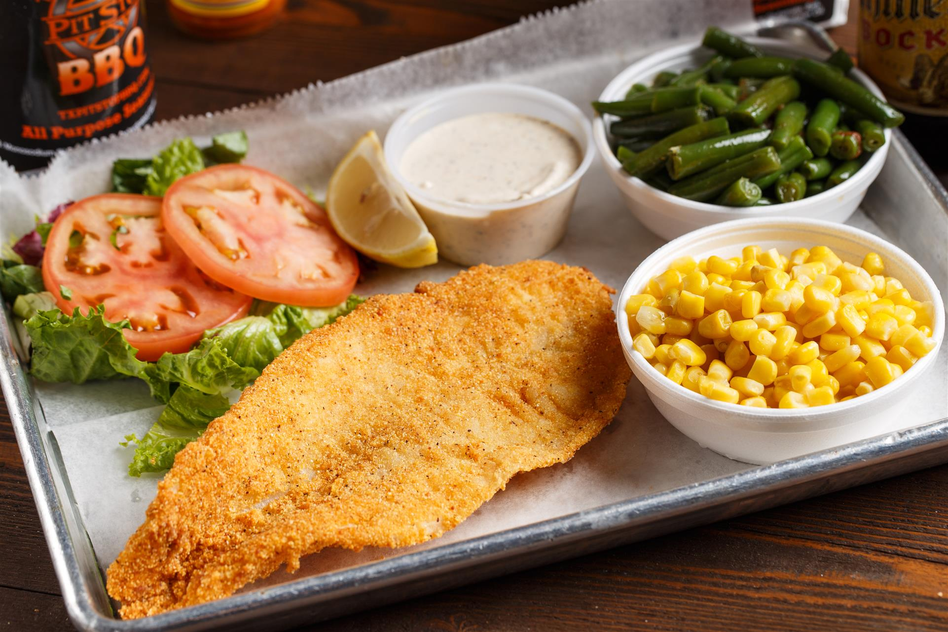 Fried fish with a side of green beans, corn, lettuce, and tomato