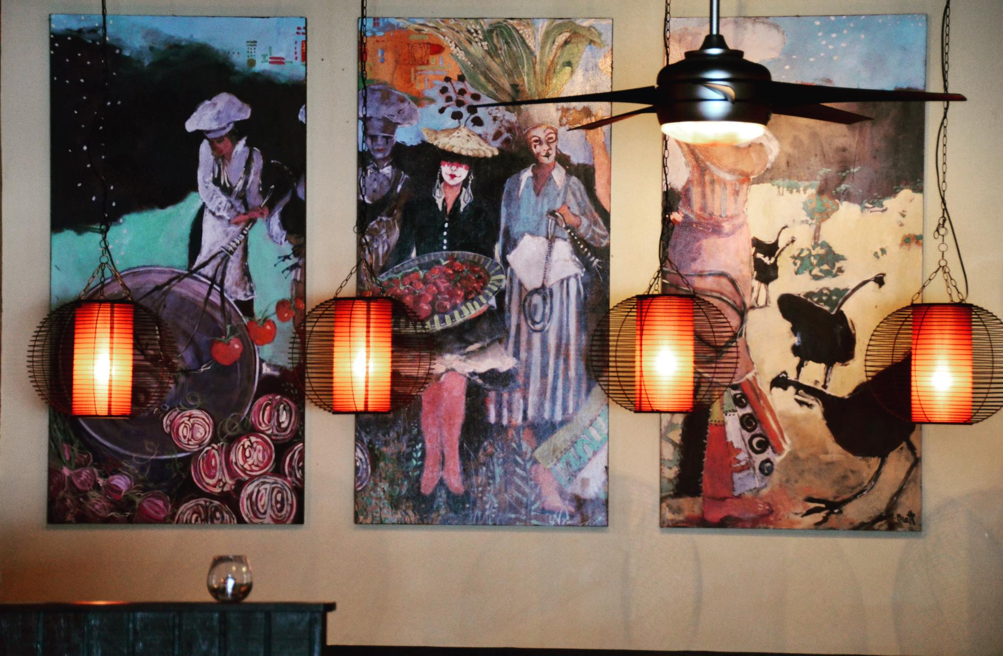 decorative wall with three paintings and light fixtures.