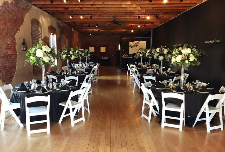 Catering room with multiple round tables decorated with fancy table settings