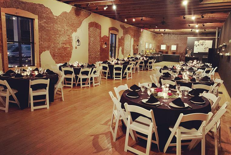 99 main catering room with multiple round tables decorated with fancy table settings