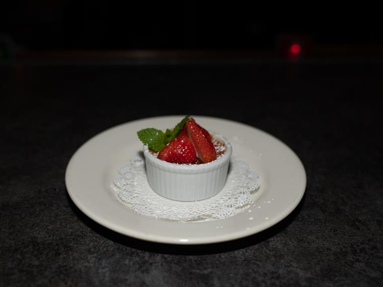creme brulee in a tin with strawberries and powdered sugar