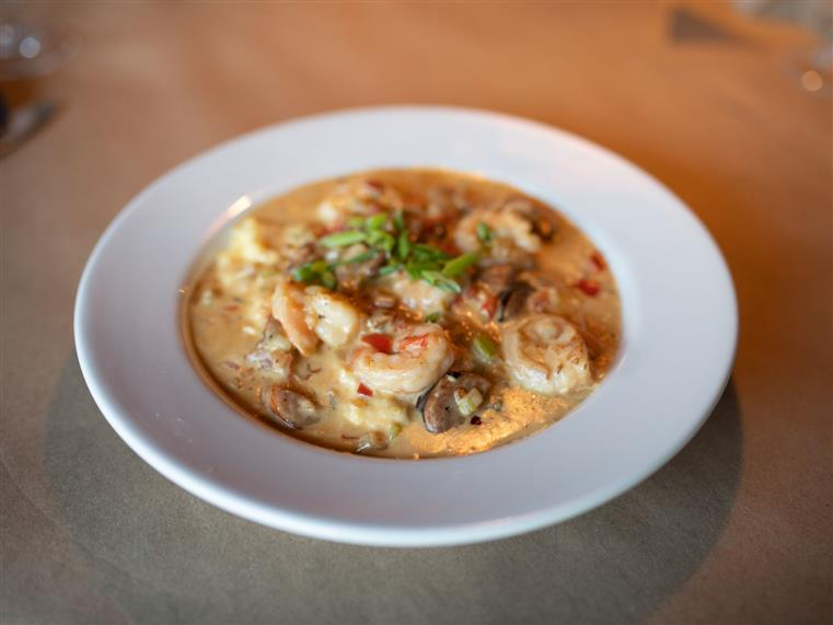 menu item with shrimp in a creamy soup and onions on top