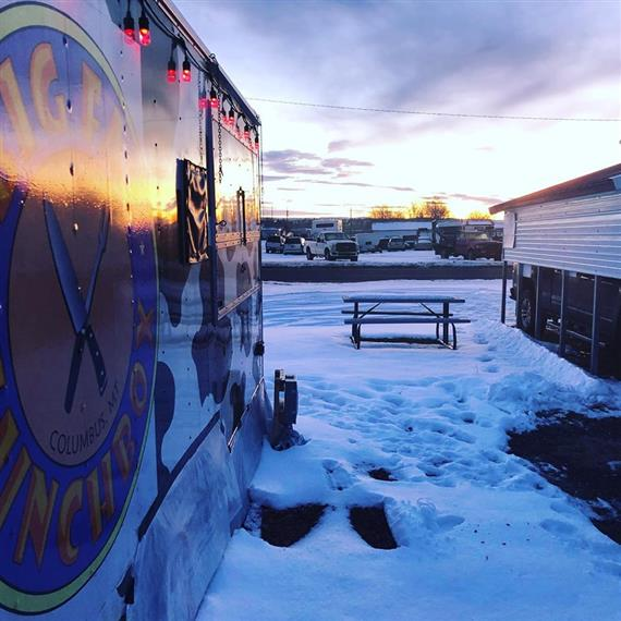 view of outside the big fat lunch box trailer with view of sunrise and snow on the ground