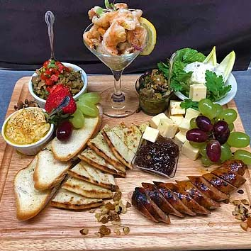 Artisanal Charcuterie Board with Cured imported Italian meats, assorted cheeses, local jam, grapes, candied nuts, herb crostini, assorted olives