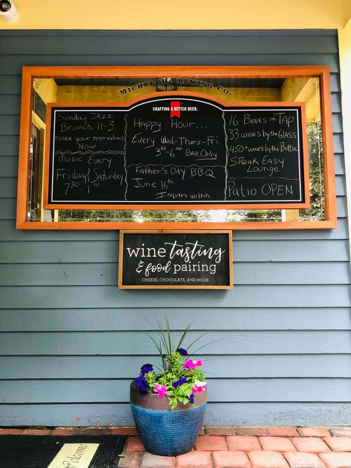 chalk board with specials and information with a flower pot beneath