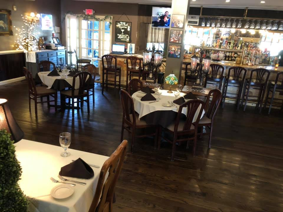 dining area with tables and chairs near the bar