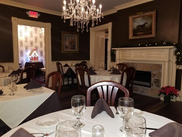 dining area with fire place and a table set with plate settings and glasses