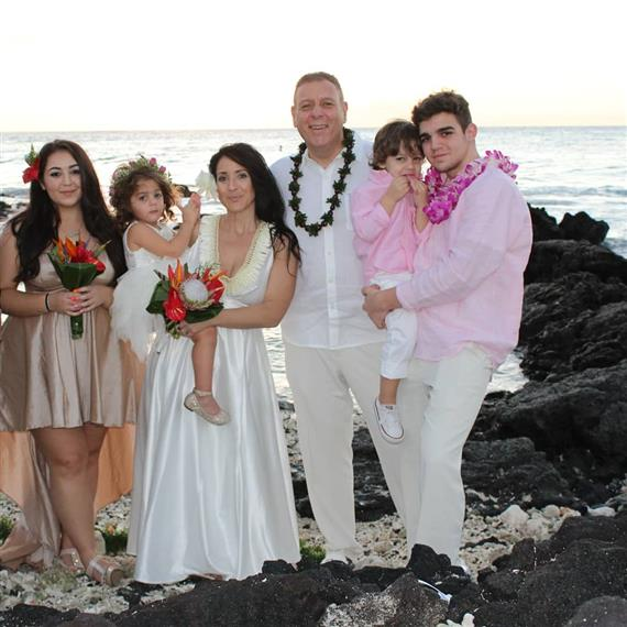 family in formal clothes at the beach