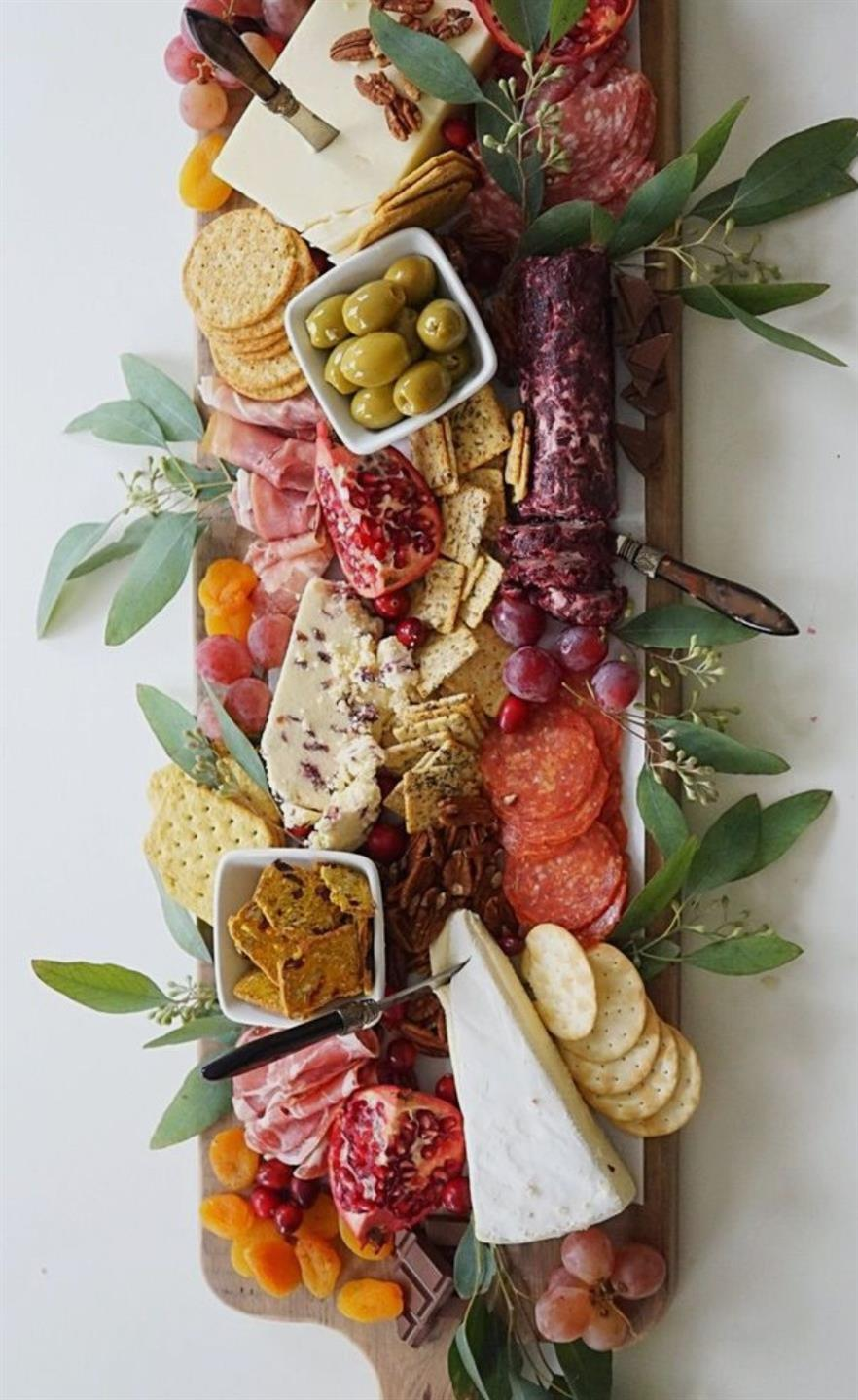 Charcuterie board full of cheeses, meats, olives and garnish