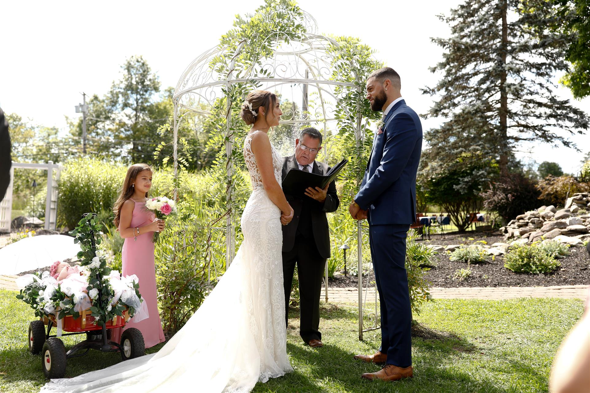 Bride and Groom with wedding officiant and bridal party outdoors
