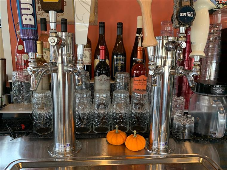 Close up of beer taps next to two small pumpkins