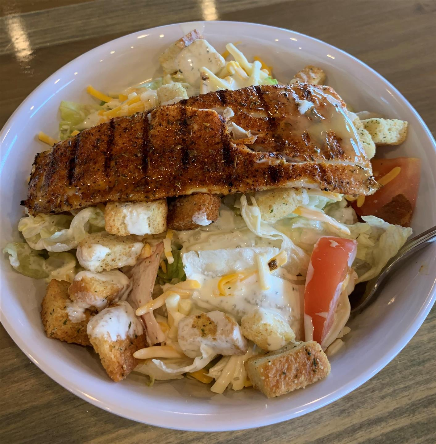 Fried fish platter on top of salad with croutons and vegetables