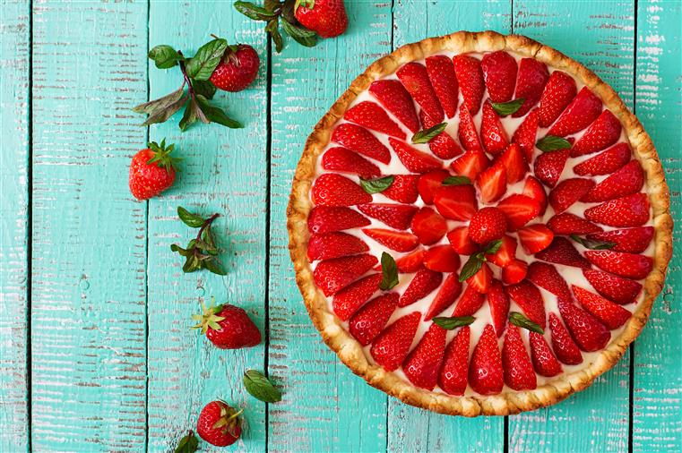 A strawberry pie topped with fresh sliced strawberries, on a table surrounded by whole fresh strawberries