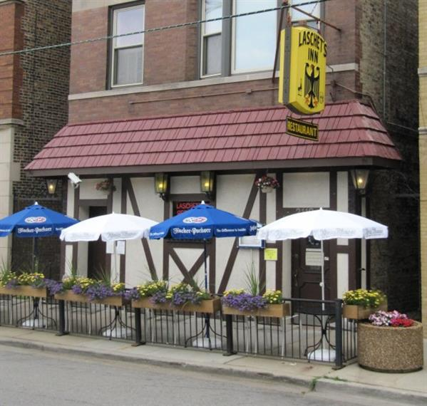 exterior of Laschet's Inn with tables, chairs and umbrellas set up