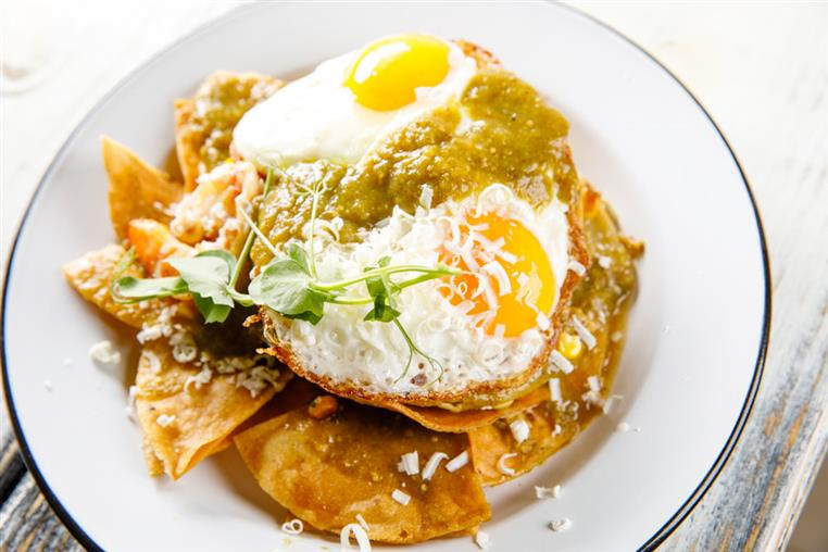 fried eggs on a plate with shredded cheese, green salsa, and tostadas