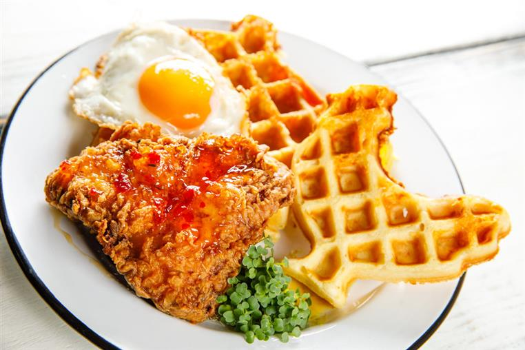 fried chicken with rooster shaped waffles served with a fried egg