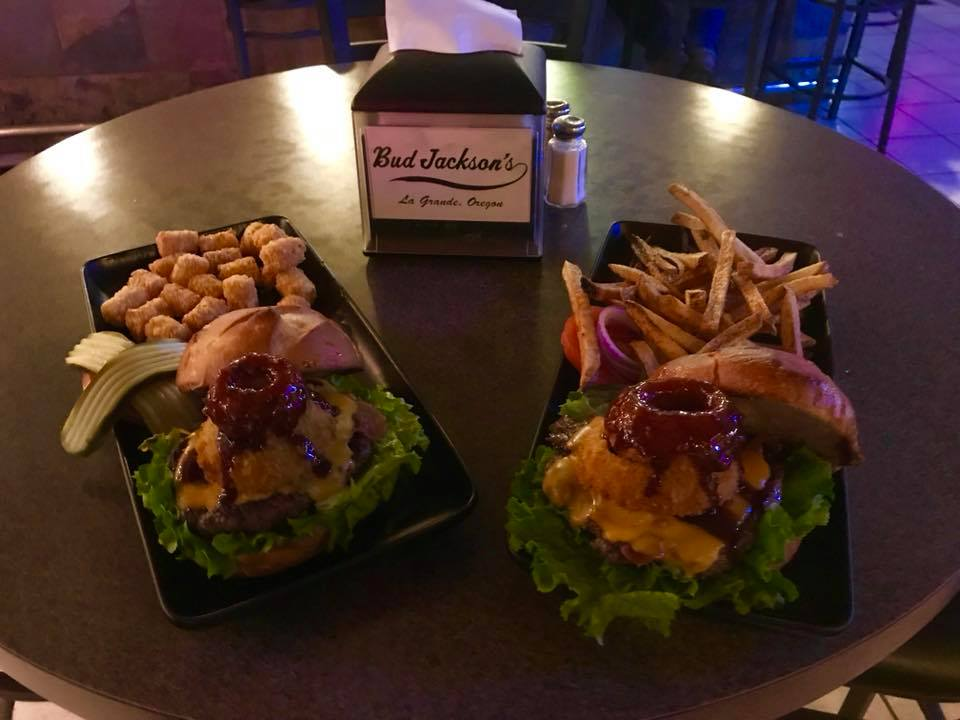Two Mountaineer Burgers stacked with bacon, cheddar cheese, onion rings and Bud's BBQ sauce. French fries and tater tots on the side.
