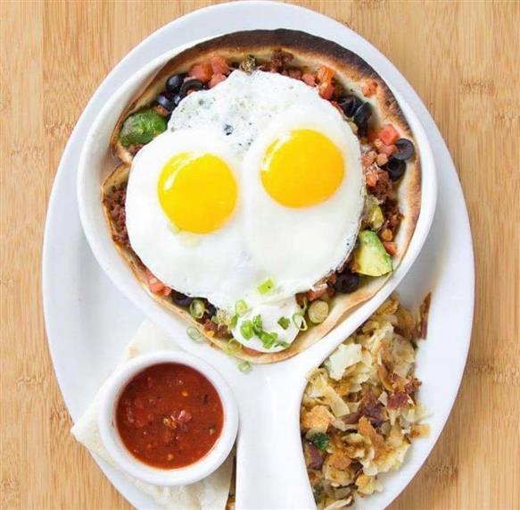 Breakfast bowl topped with two sunny-side up eggs with a side of home fries and salsa