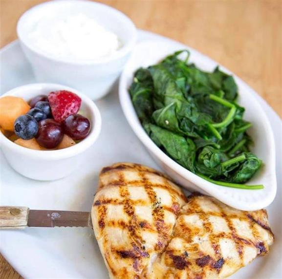 Grilled chicken with a side of spinach, yogurt, and fruit salad