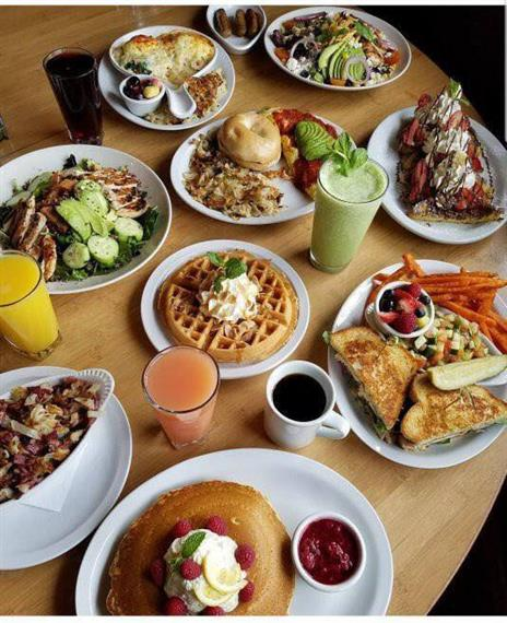 A table full of cups of juice and various meals, such as waffles, salads, pancakes, crepes