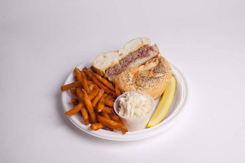 roastbeef and cheese sandwich on a plate with sweet potato fries, a pickle, and coleslaw