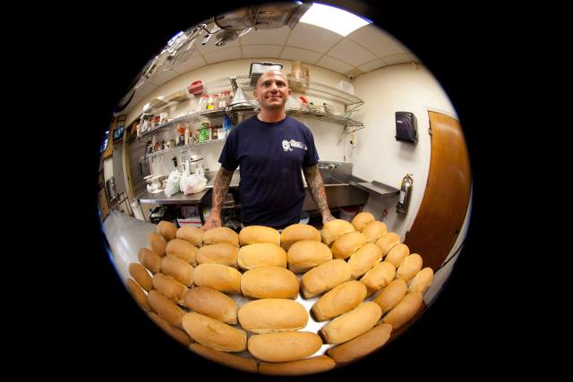 fish eye lense of employee standing in front of rolls on table