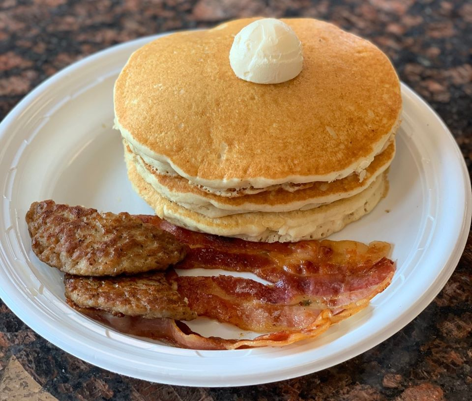stack of pancakes with butter with a side of bacon and sausage on a plate