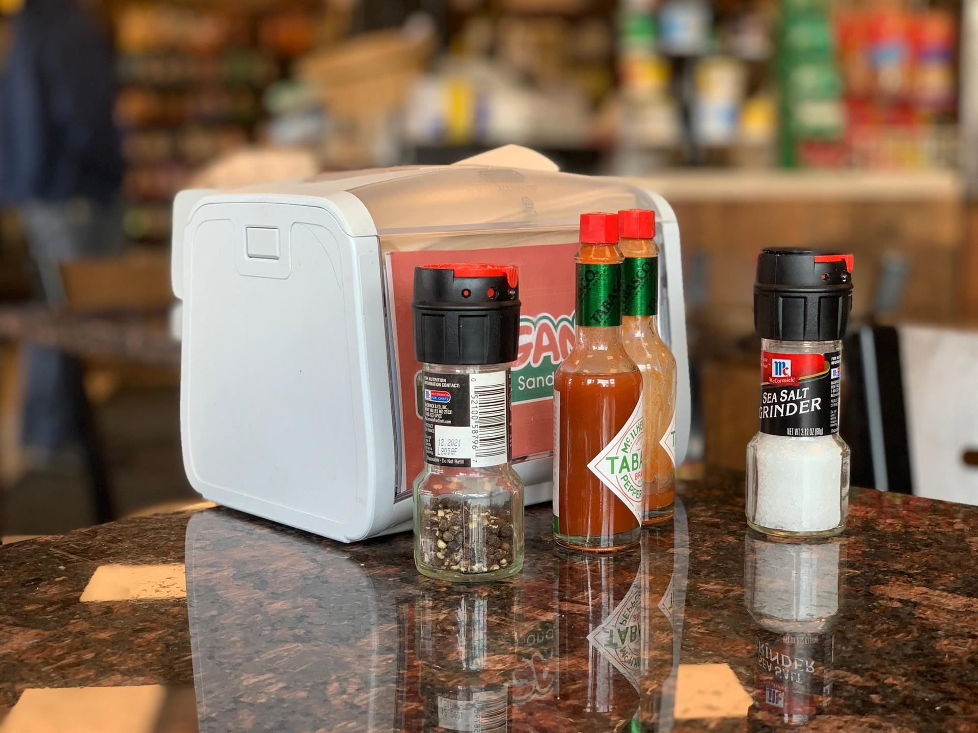 napkin holder with salt, pepper, and two bottles of hot sauce on a table