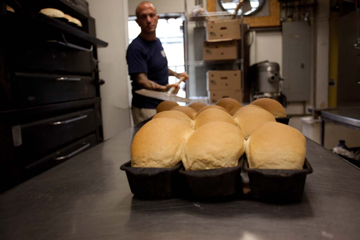 assortment of bread in baking pan with an employee in the back