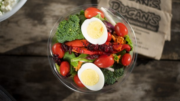 bowl filled with broccoli, tomatoes, red onion and hard boiled eggs