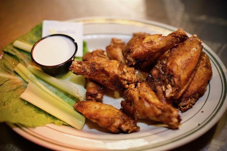 Chicken wings on a plate with a side of celery