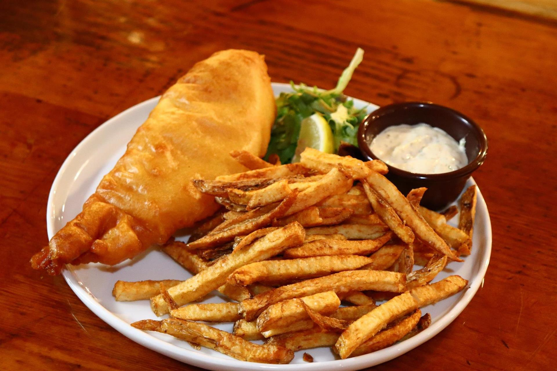 fish and chips on a plate with tartar sauce on the side.