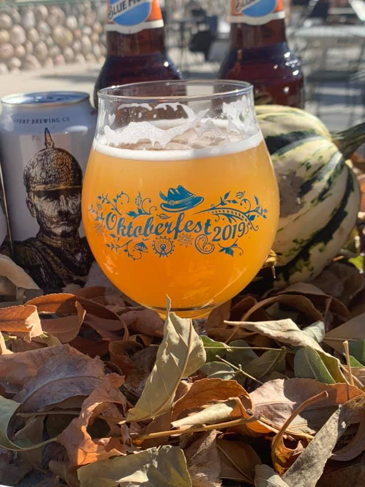 light beer in a tier glass surrounded with leaves.