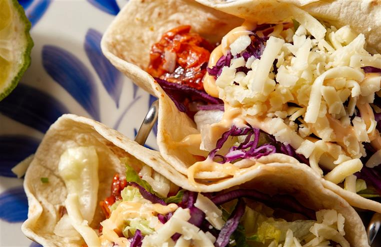 two soft tacos with meat, cabbage, shredded cheese and chipotle mayo.